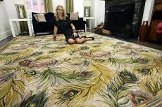 Die Modedesignerin Nanette Lepore sitzt auf einem Teppich mit Pfauenart in ihrem Zuhause in New Yorks Greenwich Village.