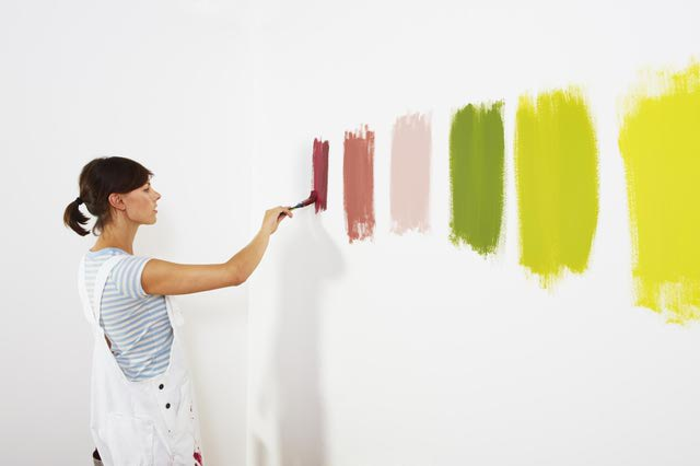 woman painting samples on wall