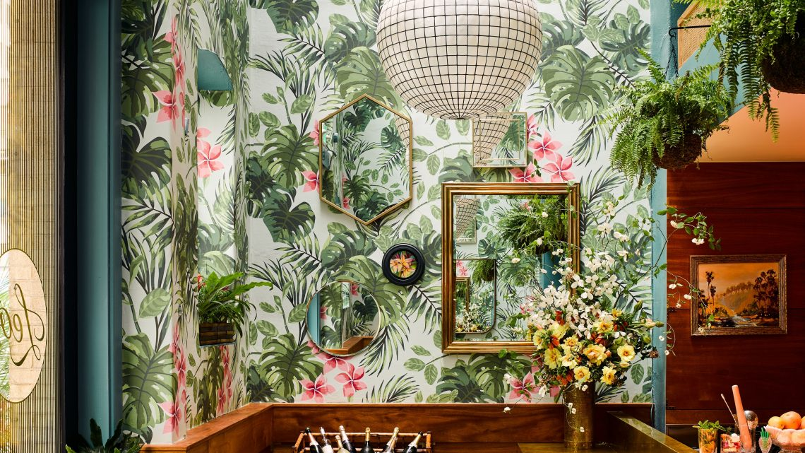 gold framed mirrors tropical pattern wallpaper